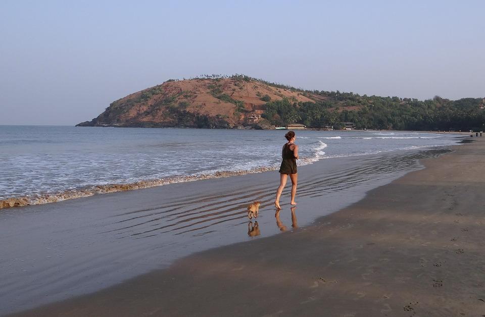 Eine Frau läuft mit ihrem Hund. Sie können mit Ihrem Hund unter allen Bedingungen laufen, auch am Meeresstrand.
